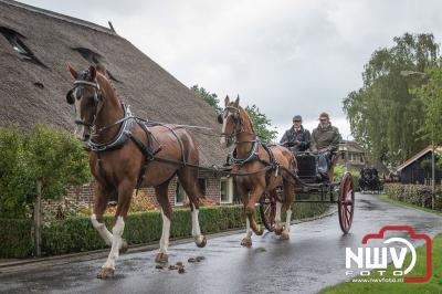 Met regenkleding aan op de bok tijdens de historische koetsentocht Elburg. - ©NWVFoto.nl
