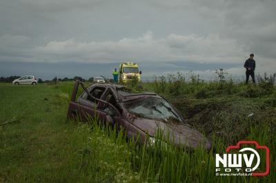 Bestuurder kan zelf uit auto komen nadat hij een aantal koprollen met zijn auto in de sloot had gemaakt. - ©NWVFoto.nl