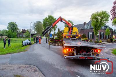 Berger moet auto weer op de weg zetten, nadat de bestuurster bij het achteruit rijden in een greppel belandde. - © NWVFoto.nl
